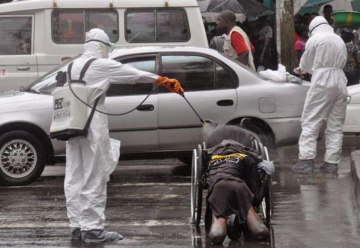 Los trabajadores de salud rocían con desinfectante el cuerpo de un hombre que se sospecha murió por el virus ébola, en una calle muy transitada en Monrovia, Liberia. (Agencias)