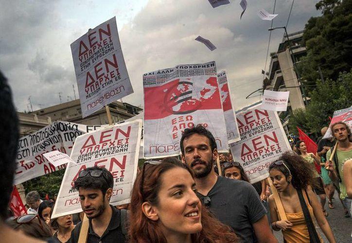 """Los miembros de los partidos de izquierda sostienen pancartas en griego que dicen """"No hay futuro en la Unión Europea"""" durante una protesta en Atenas. El primer ministro griego Alexis Tsipras dice el Banco de Grecia recomendó a los bancos cerrar y restringir transacciones por la crisis. (AP Photo/Daniel Ochoa de Olza)"""