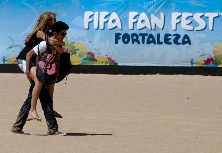 """Un hombre lleva cargando a su novia frente a un cartel que promueve el complejo donde se realizará el denominado """"Fan Fest"""" de la FIFA en Fortaleza, Brasil. (Agencias)"""
