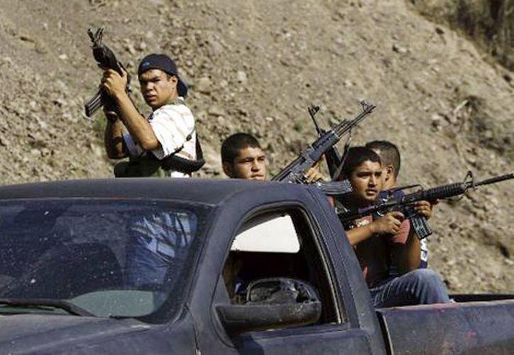 Integrantes de las autodefensas, de camino a Las Golondrinas, en Michoacán, con armamento de alto calibre. (Daniel Cruz/Milenio)