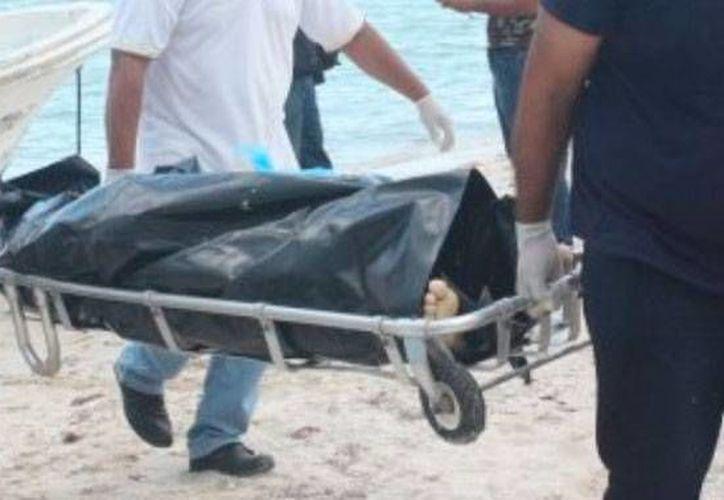 Momento en que el cuerpo del pescador Pedro Vargas Enríquez bajado a la playa; murió, víctima de un infarto, cuando estaba en altamar. (Óscar Pérez/SIPSE)