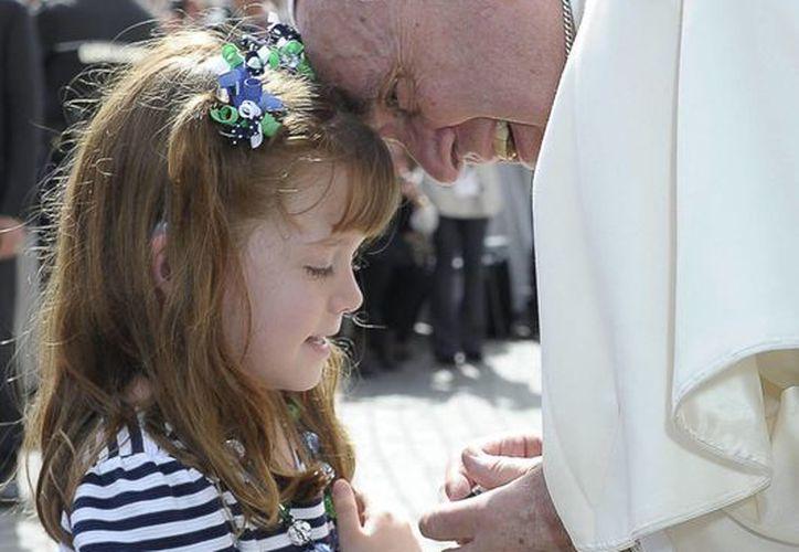 El papa Francisco conversa con la joven Lizzy Myer durante la audiencia general de los miércoles en la Plaza de San Pedro en el Vaticano. (EFE)