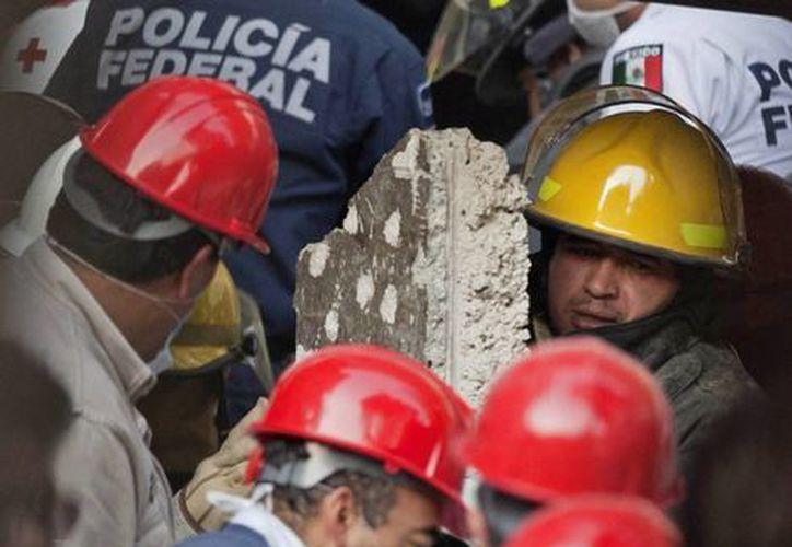 Un trabajador de emergencia carga una losa de concreto, mientras varios compañeros buscan a sobrevivientes en la Torre de Pemex. (Agencias)