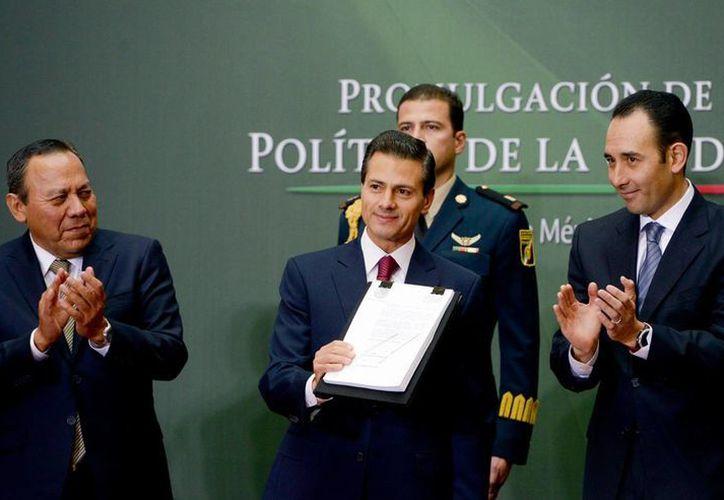 El presidente Enrique Peña Nieto promulgó este viernes la reforma política de la Ciudad de México, en  Palacio Nacional. En la imagen, flanqueados por los presidente de las cámaras de Diputados, Jesús Zambrano, y de Senadores, Roberto Gil Zuarth. (Notimex)