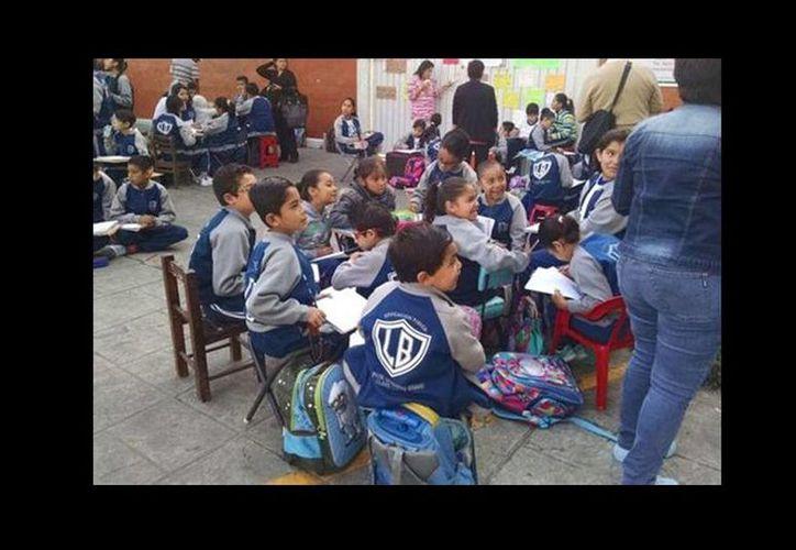 Los maestros cesados, apoyados por padres de familia, dan clases a los alumnos de una escuela en Peralvillo sobre Calzada Misterios. (César Velázquez/Milenio)
