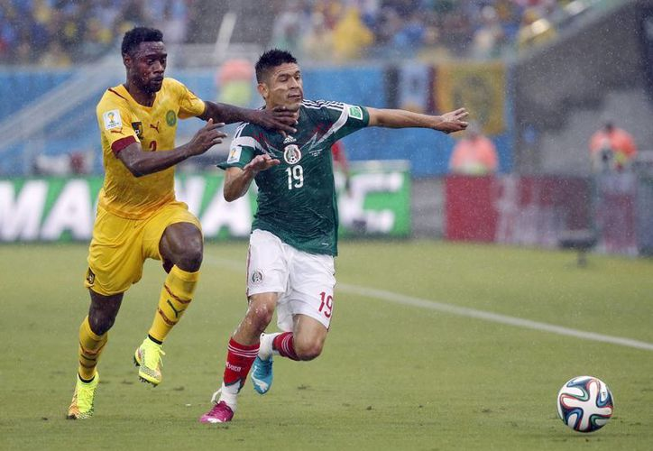 Oribe Peralta disputa el balón con Benoit Assou-Ekotto en el primer tiempo del partido entre México y Camerún en el Mundial. (Foto: AP)