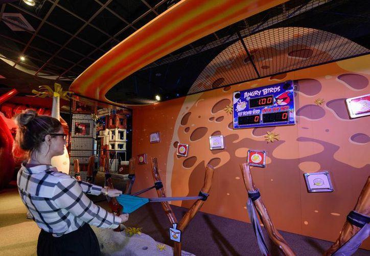 Una visitante da su mejor esfuerzo en una competencia con otros jugadores en el centro Angry Birds Space Encounter en el complejo de visitantes del Centro Espacial Kennedy en Cabo Cañaveral, Florida. (Agencias)