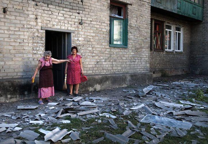 Imagen de dos mujeres a las afueras de un edificio donde vivían en Donetsk y que fue bombardeado. (Agencias)