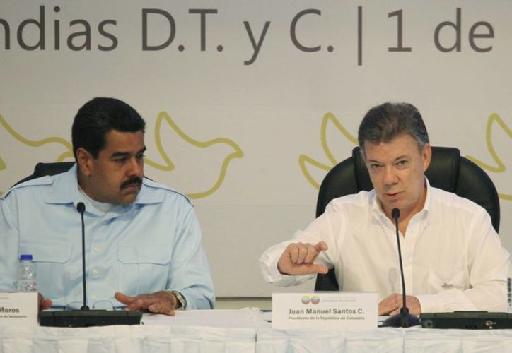 El presidente de Colombia, Juan Manuel Santos, a la derecha, acompañado del presidente de Venezuela, Nicolás Maduro, a la izquierda, durante una reunión bilateral en Cartagena. (Agencias)