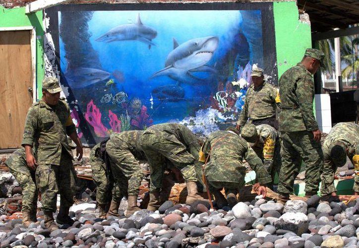 """La Sedena es una de las dependencias a las que menos recursos se recortarán de su presupuesto en 2016. En la imagen, soldados apoyan a la población de Paraíso, Colima, tras el paso del huracán """"Patricia"""". (Foto de archivo/Notimex)"""