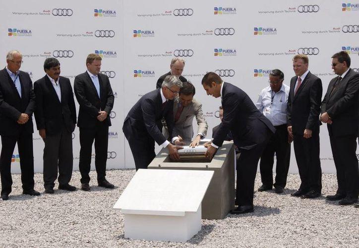 El secretario de Economía, el gobernador de Puebla y directivos de la empresa automotriz al  colocar la primera piedra de la obra. (Notimex)