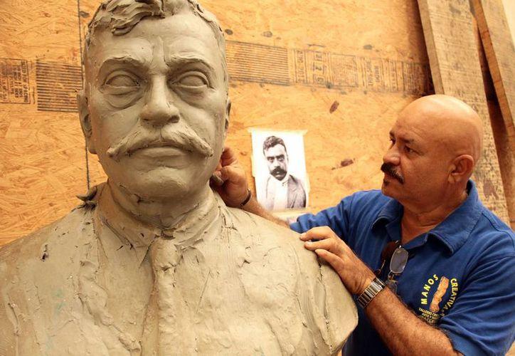 Desde los cuatro años, el talento de Reynaldo Bolio 'Paccelli' hacia las artes plásticas, comenzó a manifestarse. Imagen del escultor con una de sus obras.(Jorge Acosta/SIPSE)