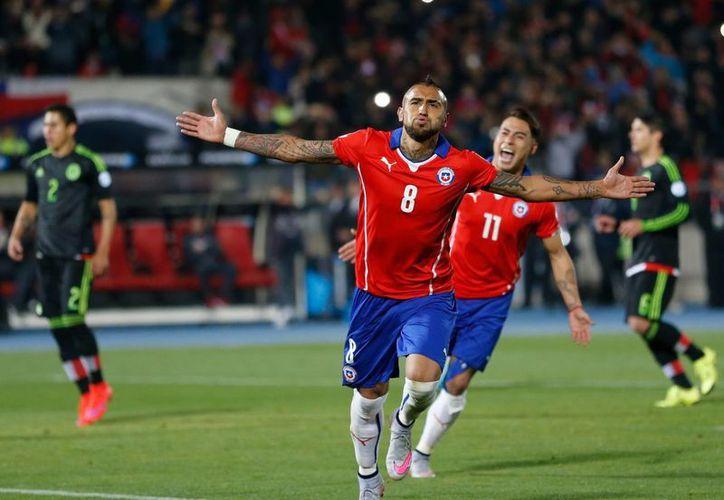 Arturo Vidal, quien en la foto celebra uno de los 2 goles que le metió a México en el 3-3, está hospitalizado porque este martes por la noche sufrió un accidente automovilístico. (Foto: AP)