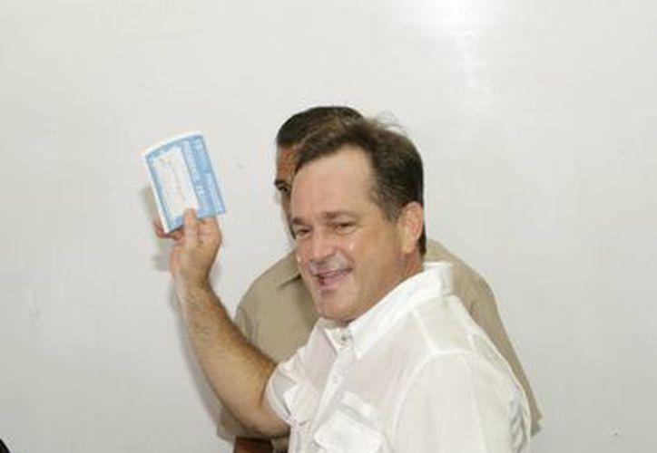 Juan Carlos Navarro, candidato presidencial del Partido Revolucionario Democrático, muestra su voto antes de depositarlo en una urna electoral en Ciudad de Panamá. (AP)