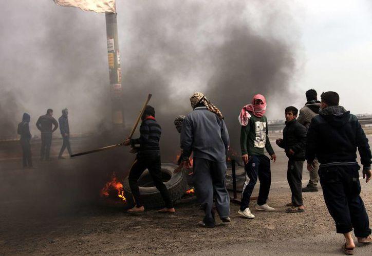 Manifestantes enmascarados sunitas iraquíes queman neumáticos para bloquear la carretera principal que va a  Jordania y Siria. (Argencias)