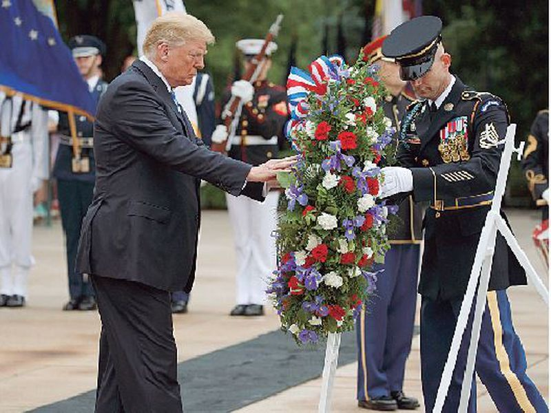 President Donald Trump lays a wreath at the Tomb of the Unknown Soldier at Arlington National Cemetery, in Arlington, Va.