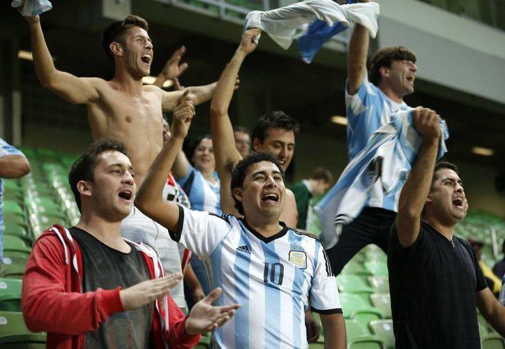Fans de la Selección Argentina apoyan a los jugadores durante una sesión de entrenamiento previo a su debut en el Mundial de Brasil 2014. (Foto: AP)