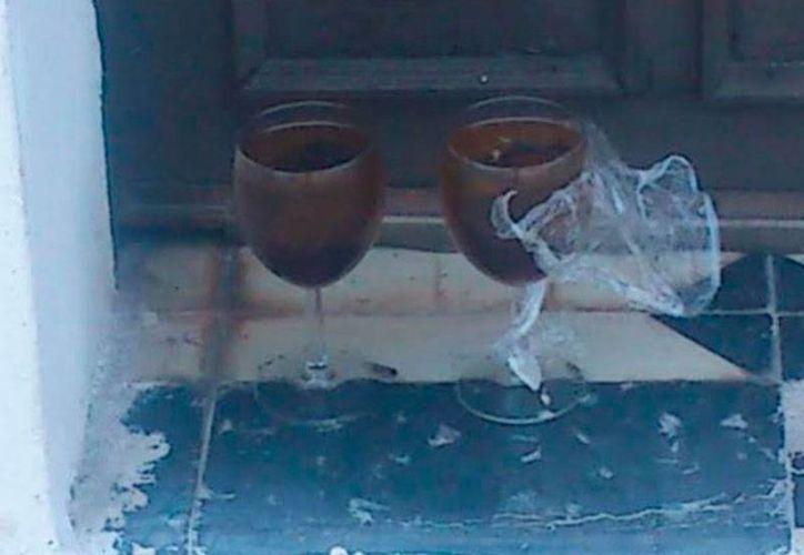 Vecinos del rumbo de la iglesia de San José, al oriente de la ciudad de Progreso, interpretaron los objetos (dos copas con líquido oscuro y papeles con nombres de 2 personas) que alguien colocó a las puertas de la iglesia como un 'trabajo' de brujería. (Óscar Pérez/SIPSE)