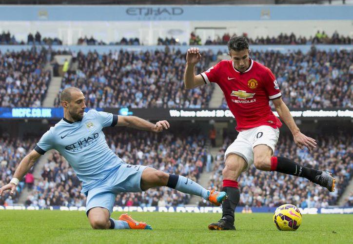 El Manchester City impuso su condición de local al derrotar al ManU; en la imagen, el duelo por el balón entre Pablo Zabaleta y Robin van Persie. (AP)