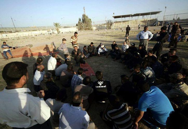Voluntarios chiíes participan en un entrenamiento físico en un centro de reclutamiento de voluntarios en Kerbala, en el sur de Irak, este martes 24 de junio de 2014. (EFE)
