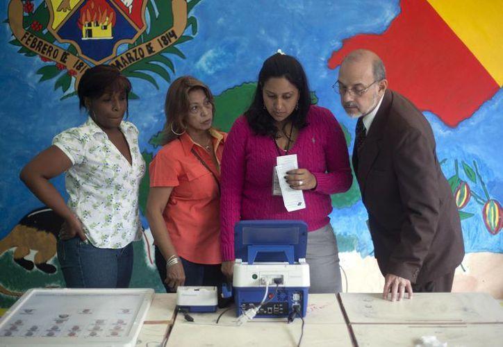 Funcionarios electorales verifican una máquina de votación para las elecciones del domingo. (Agencias)