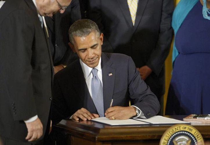 El presidente de Estados Unidos, Barak Obama, firma la Orden Ejecutiva para proteger a los empleados con condición de gays, lesbianas, bisexuales y transexuales, de discriminación en su trabajo, en la Casa Blanca, en Washington, DC, EU. (EFE)