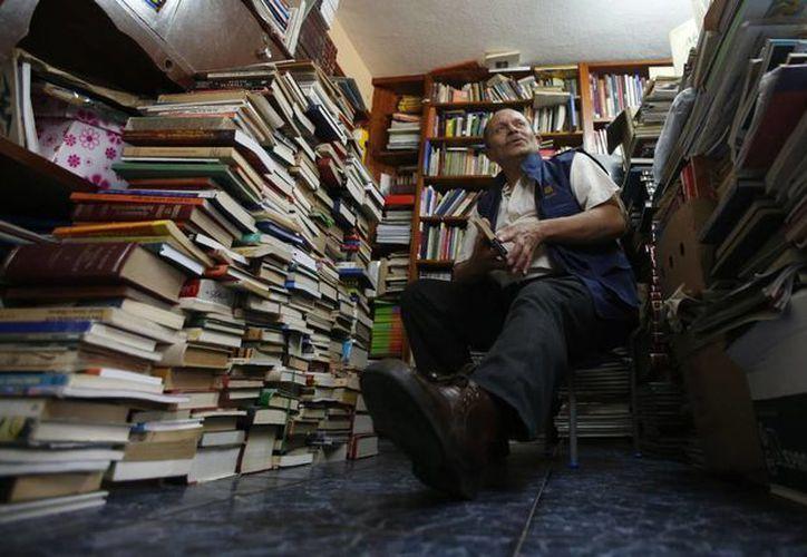 José Alberto Gutiérrez posa en medio de pilas de libros en su casa de Bogotá, en Colombia. (Agencias)