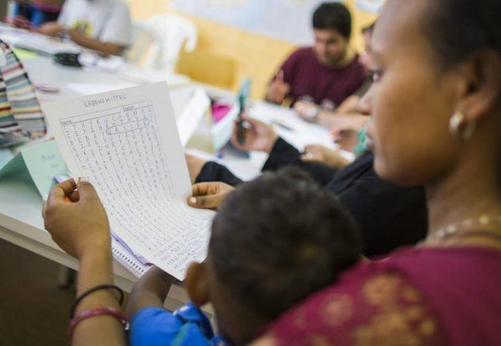 Foto de inmigrantes en un curso de alemán en un centro de primera admisión de refugiados en el distrito berlinés de Gatow, Alemania. (Agencias)