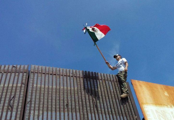 Un joven ondea la bandera mexicana montado sobre la barda que divide a México de Estados Unidos. Imagen de contexto. Archivo/EFE)