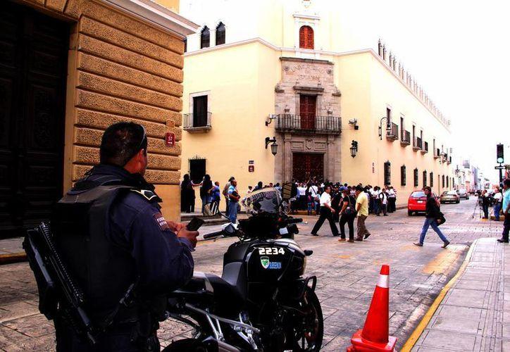 Un agente de la Policía Municipal observa la protesta y huelga de trabajadores en el Edificio Central de la UADY. (José Acosta/SIPSE)