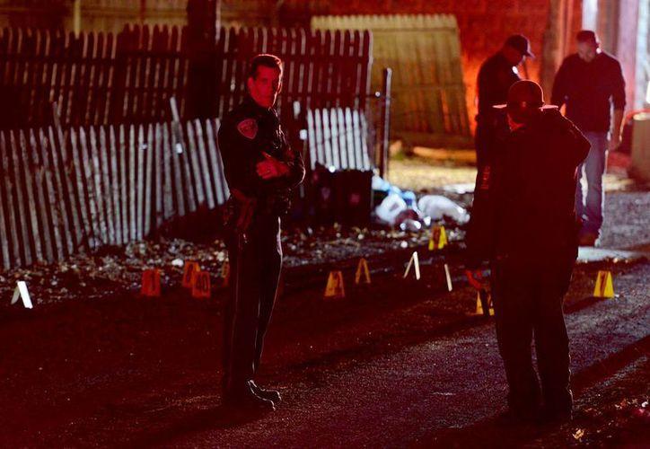 La policía investiga la escena de un tiroteo en un suburbio de Pittsburgh, la policía asegura que dos personas emboscaron la casa para disparar a los invitados. (Michael Henninger / Pittsburgh Post-Gazette través AP)
