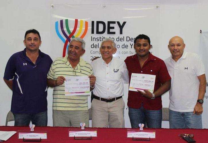 Juan Sosa Puerto, director del Idey, entrega los cheques a los campeones Artesanos de Ticul, que se coronaron en la Liga de Invierno Naxón Zapata de Beisbol. (Milenio Novedades)