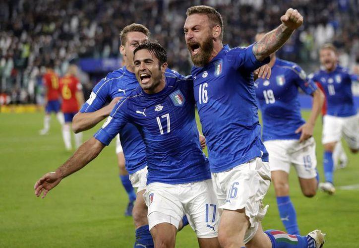 Italia sumó un punto importante para seguir en los primeros lugares del grupo G. En la foto, De Rossi celebra la anotación del empate.(Antonio Calanni/AP)