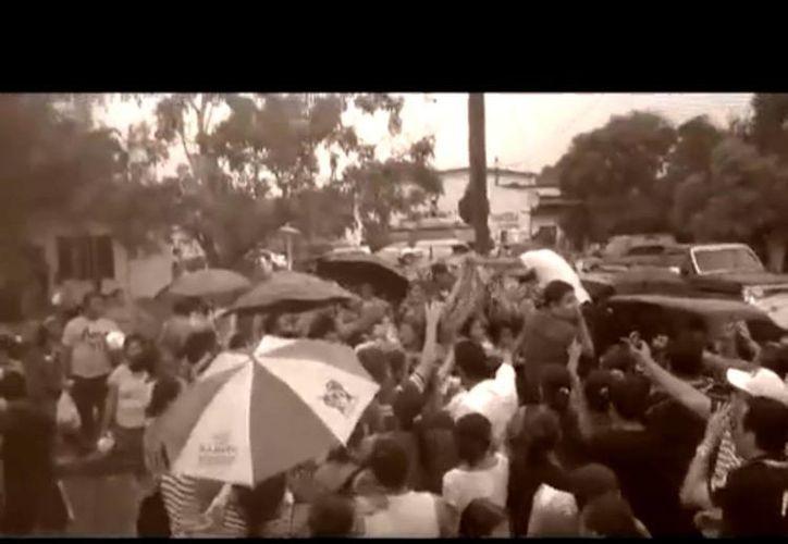 En el video se aprecia a una multitud esperando a recibir despensas. (Captura de pantalla de YouTube)