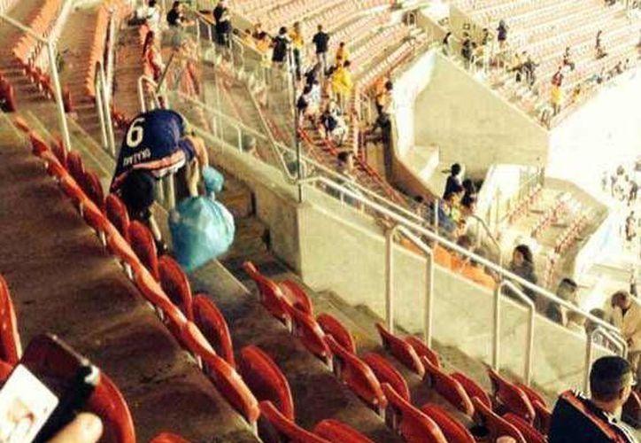 Mucha gente dejó tirada su basura en el estadio de Recife, pero un grupo de japoneses por voluntad propia se puso a limpiar. (Foto: especial)