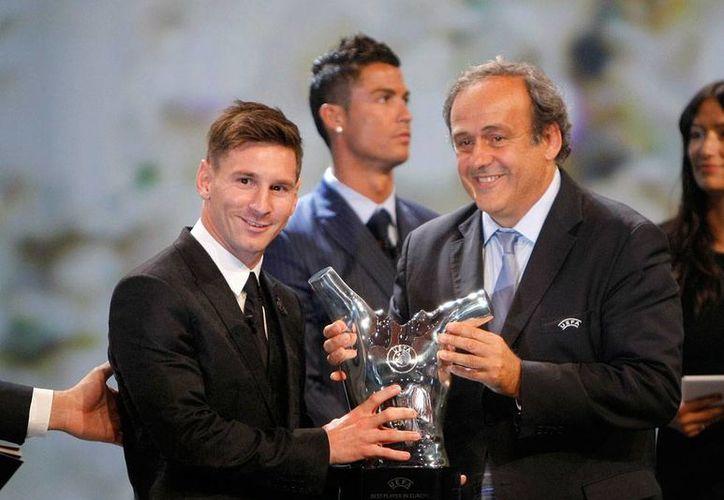 Lionel Messi (izq.) recibió de manos de Michel Platini, el galardón como el mejor jugador de Europa, durante la gala en la que también se sortearon los lugares de la Champions League. (AP)