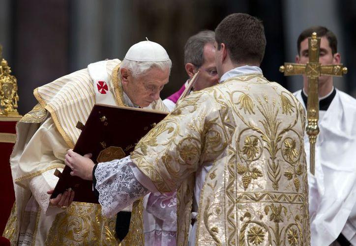 El Papa Benedicto XVI besa el santo Evangelio durante una misa en el Vaticano para celebrar la Epifanía. (Agencias)