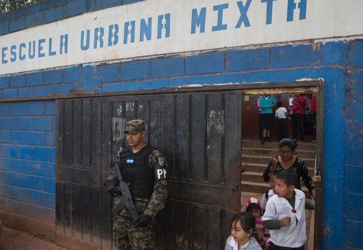 Un policía militar monta guardia frente a una escuela en el último día de clases en el barrio Canaan de Tegucigalpa. (Agencias)