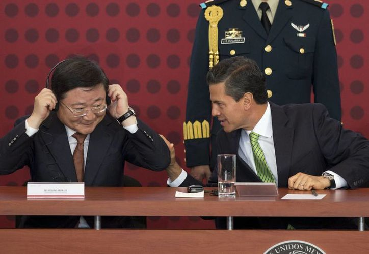 El presidente Enrique Peña Nieto hace un comentario al vicepresidente y CEO de KIA, Hyoung-Keun Lee, en el evento en que se anunció la inversión de KIA Auto, hoy en Monterrey, Nuevo León. (Agencias)