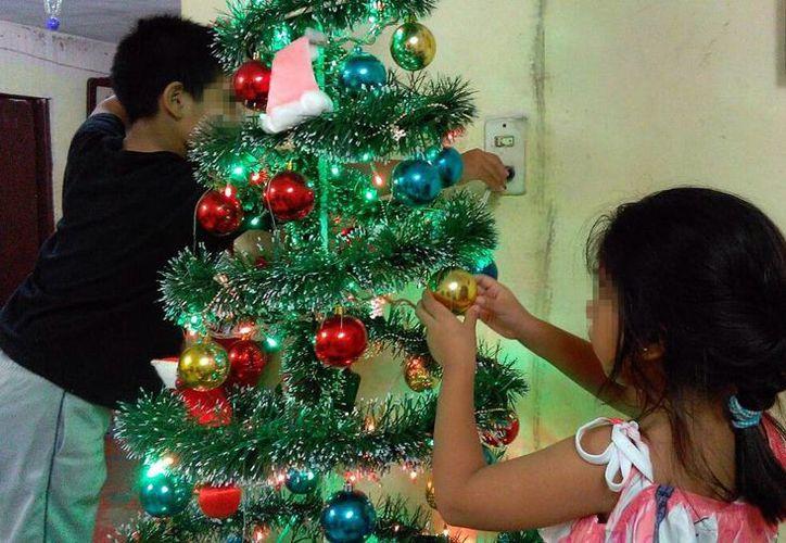 Recomiendan extremar precauciones tanto en el hogar como en la vía pública. Imagen de contexto de dos niños que adornan un árbol de Navidad. (Milenio Novedades)