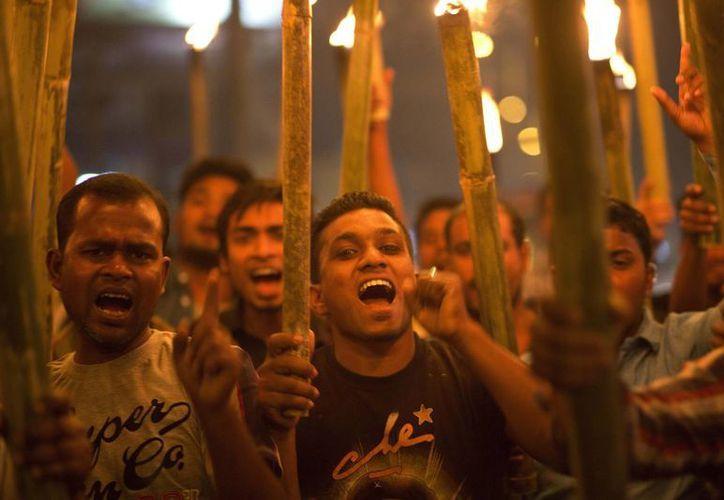 Activistas gritan consignas durante una protesta contra el linchamiento de un hombre acusado de violación en Gauhati, en el estado indio nororiental de Assam. (Agencias)