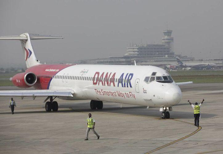 Personal en tierra de la aerolínea Dana hace señales al piloto durante la demostración de un vuelo de Lagos a Abuja con celebridades, periodistas y directivos de la empresa en el aeropuerto Murtala Muhammed en Lagos, Nigeria. (Agencias)