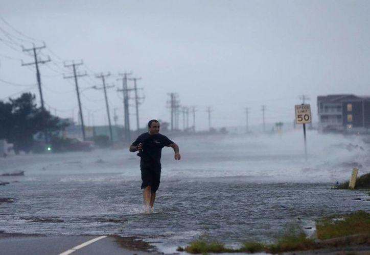 Un hombre cruza un tramo inundado de la autopista 64 mientras el huracán Arthur cruza Nags Head, Carolina del Norte. (AP)
