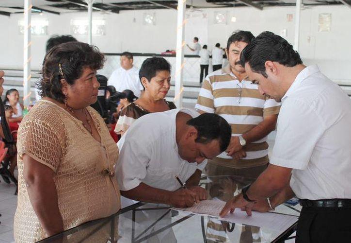 Las parejas fueron pasando para firmar sus respectivas actas de matrimonio. (Cortesía/SIPSE)