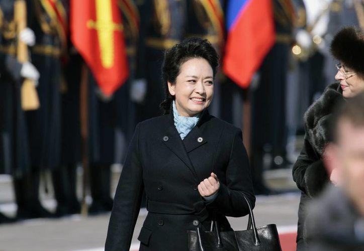 Peng Liyuan, esposa del presidente chino Xi Jinping, sonríe a su llegada al aeropuerto Vnukovo II, en las afueras de Moscú, Rusia. (Agencias)