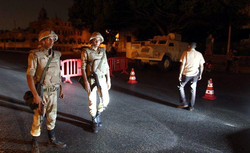 Las Fuerzas Armadas egipcias inspeccionan vehículos en un retén de control durante el toque de queda establecido, en Heliopolis, Egipto. (EFE)