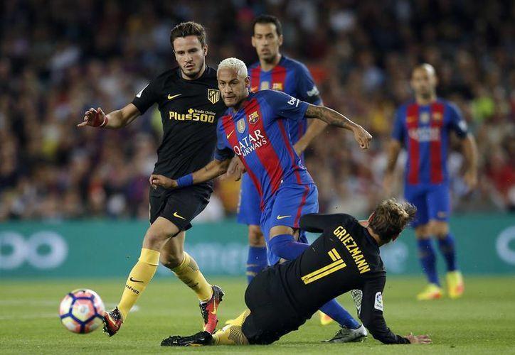 Neymar (de frente) enfrenta a Griezmann en partido entre Barza y Atlético que terminó 1-1. (AP)