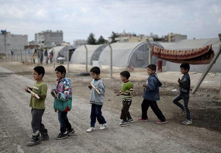 Niños refugiados sirios procedente de Kobani, juegan a ser soldados en un campo de refugiados en el distrito de Suruc, Turquía. (Archivo/EFE)