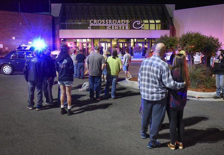 Gente de pie junto a la entrada norte del centro comercial Crossroads, entre Macy's y Target, mientras la policía investiga el apuñalamiento múltiple. (Dave Schwarz/St. Cloud Times via AP)