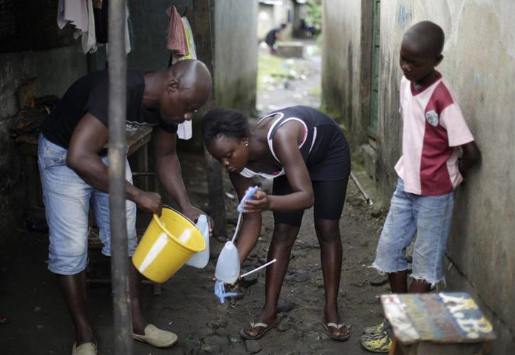 Un activista ayuda a una joven, que quedó huérfana junto con su hermano, tras la muerte de sus padres por el ébola, a llenar una botella con cloro en St. Paul Bridge en Monrovia, Liberia. (Agencias)